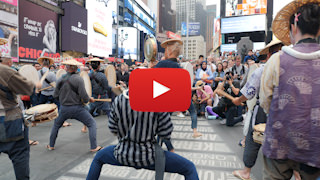 Japanese men playing instrunments  for a mob of people  in New York City