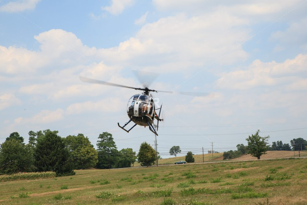Helicopter landing in a field by trees in the country side