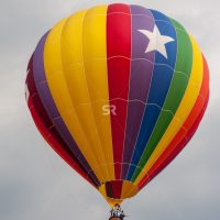 A hot air balloon with a pattern design on a cloudy day