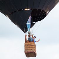 Two people blowing hot air into their balloon in the air