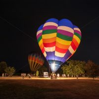 Several people  lighting a hot air balloon for take off at night