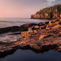 Pink granite along the Maine coast glow in the new morning sunrise light