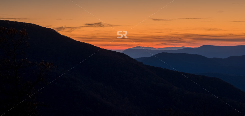 Black silhouette mountain with sweet colorful sky after sunset in winter season.