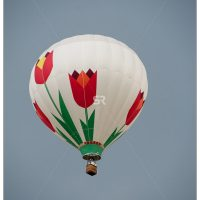 White flower covered hot air balloon flying high in the sky