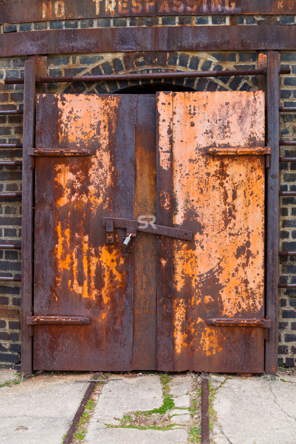 Old metal door that has been rusted over time locked
