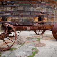 Old rusted wagon by and old brick building on a cloudy day