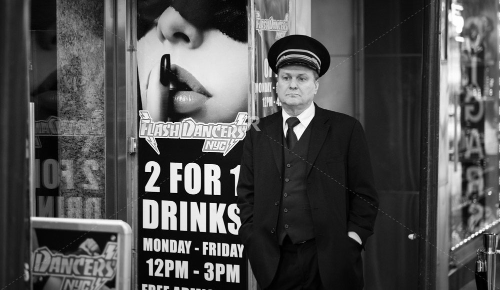 White man in uniform standing outfront waiting   inTimes Square NYC