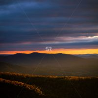 Dark sky Sunset over a beautiful valley of trees and scenery