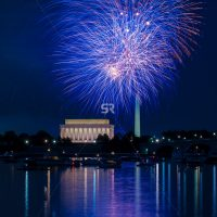Blue Fireworks launching high in the sky over the Washington Monunment in DC