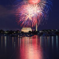 Several color Fireworks launching high in the sky over the Washington Monunment in DC