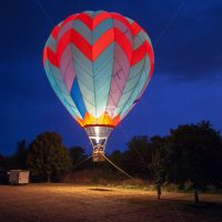 Colorful hot air ballon taking off at night