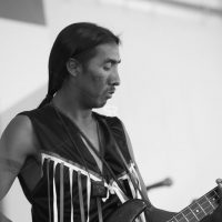 Native American playing classic shape electric guitar