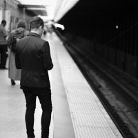 Man waiting on the station platform for the subway listening to music  inTimes Square NYC