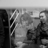 Two women sitting on the metro together happy  in Times Square NYC