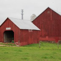 Framed shot of beautiful red barn on a grassy plane on a cloudy day