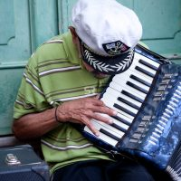 An old man plays music for money with his accordion on the streets of Old San Juan