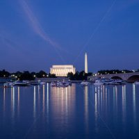Beautiful night sky over the Washington DC harbor from the river overlooking the monunment and Lincoln Memorial