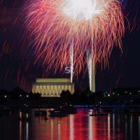 Red Fireworks launching high in the sky over the Washington Monunment in DC