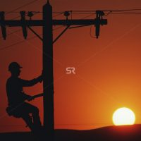 Silhouette of male working on electrical pole