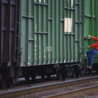 Man hanging onto side of train