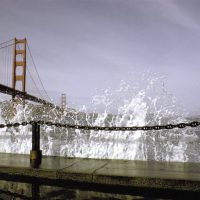 Wave hitting against concrete with Golden Gate bridge in background