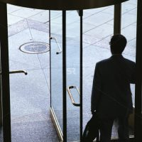 Businessman walking out of revolving door