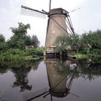 Old style windmill with reflection in water