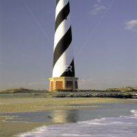 Light house on beach with waves in foreground