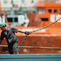 Dock worker pulling chain