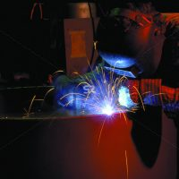 Workers weld metal