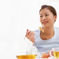 Asian woman eating orange