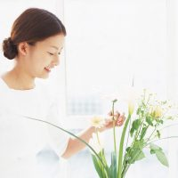 Asian woman touching flowers