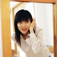 Asian woman looking at mirror