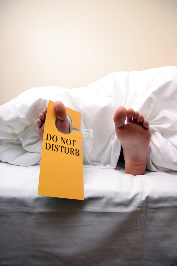 feet under covers with do not disturb sign