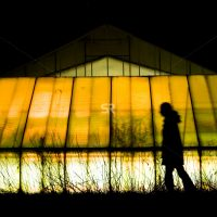 Man walking in front of green house