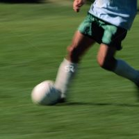 Soccer player running fast and kicking the ball with motion blur
