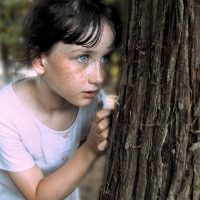 Young girl hides behind tree