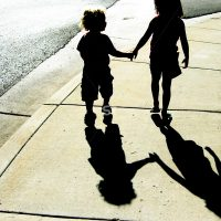 Two young kids walk and hold hands