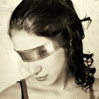 Woman blind folded with film strip