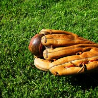 Baseball glove with ball in grass