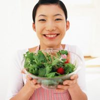 Asian woman holding salad