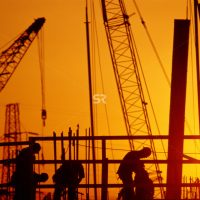 Silhouette of construction workers with cranes in background
