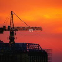 Construction site with crane during sunset