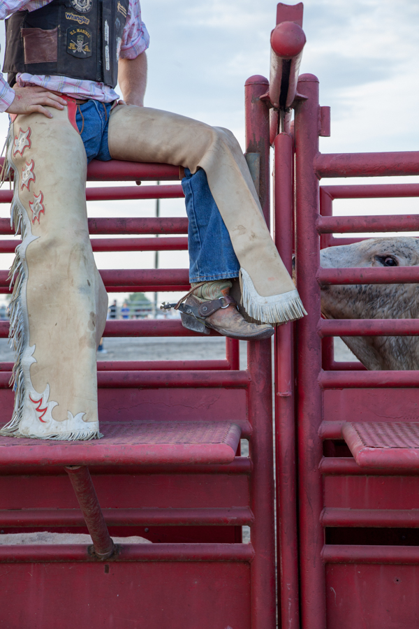 Cowboy on  boots and jeans sitting on the fance at the rodeo