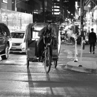 Male bike taxi driver riding around the city in NY