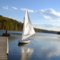 Small white boat  on a lake during the fall season