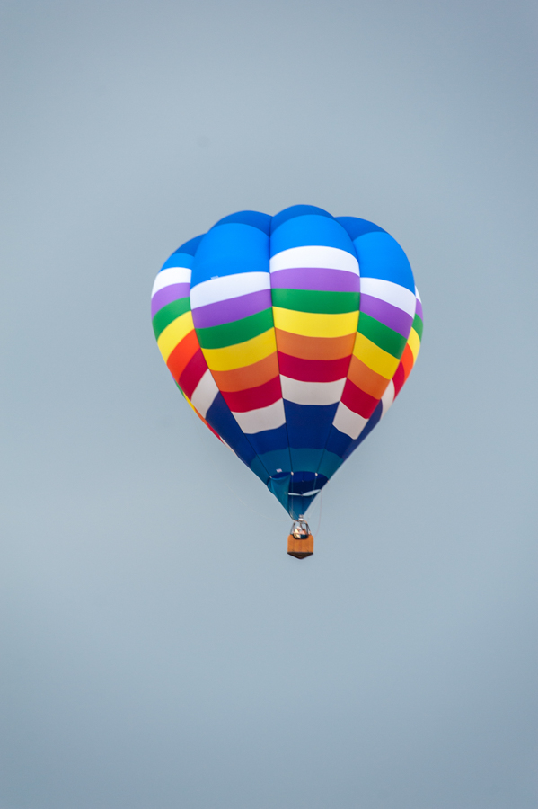 Rainbow colored hot air balloon flying high in the sky